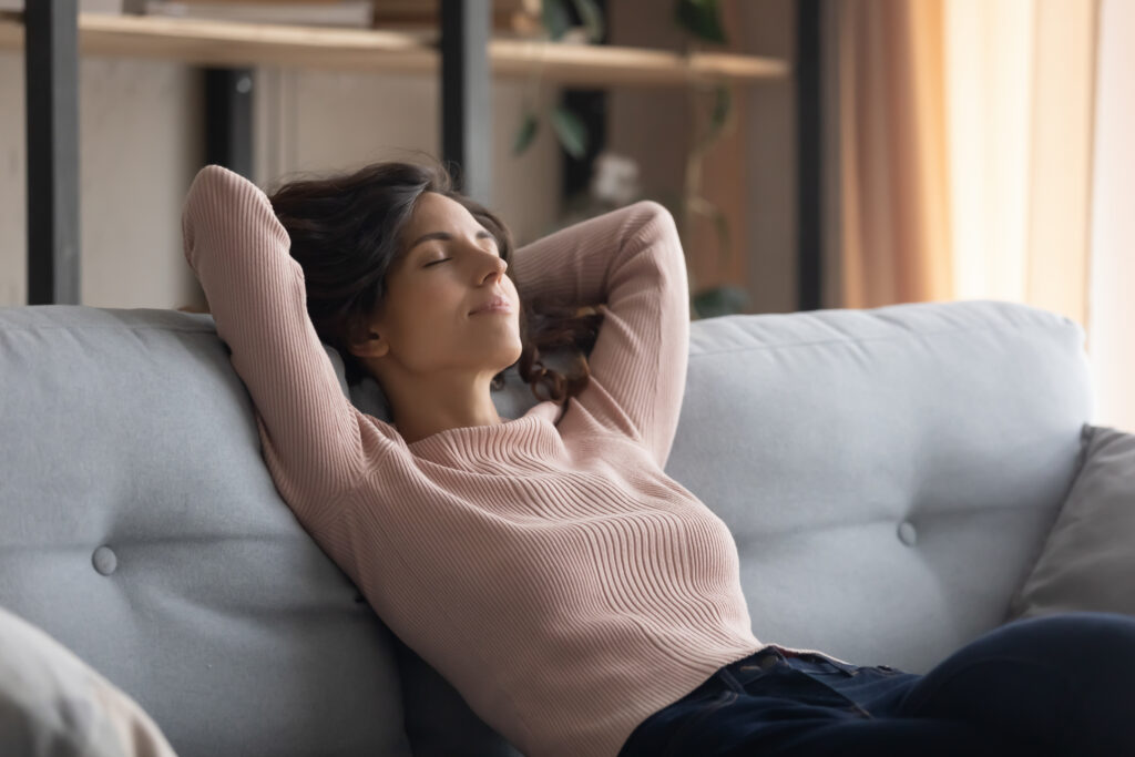 Woman resting on the sofa during a virtual hypnosis session